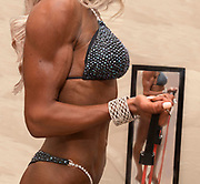 An athletic competitor checks her form in a mirror prior to going on stage.