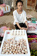 Vendor selling chicken and goose eggs on her stall at Khua Din morning market in Vientiane city, Lao PDR. A large variety of local products are available for sale in fresh markets all over Laos, all being sold on small individual stalls. Talat Khua Din is a traditional Lao market close to Vientiane city centre and is currently under threat from the construction of a shopping mall.