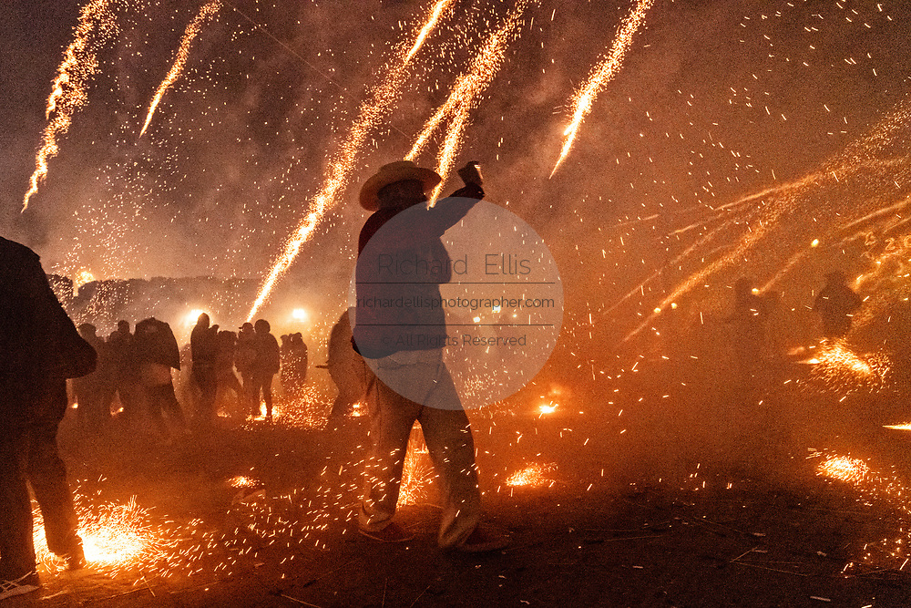 Sparks from exploding sky rockets scatter as a Mexican cowboy stands in the middle taking a mobile phone photo during the Alborada festival September 29, 2018 in San Miguel de Allende, Mexico. The unusual festival celebrates the cities patron saint with a two hour-long firework battle at 4am representing the struggle between Saint Michael and Lucifer.