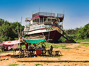 31 MAY 2016 - SIEM REAP, CAMBODIA: A small refreshment stand about 50 meters from where the Tara is beached. The Tara is a river freighter and passenger boat assembled in Vietnam, then a French colony, in 1927. Most recently it's used to take tourists on dinner cruises on the Tonle Sap Lake. Because of the drought in Cambodia, the Tara is beached and unable to navigate the nearly empty canals that lead to the Tonle Sap Lake. The boat's owners are repairing and refurbishing it while it's beached and hope that the coming rainy season will flood the canal enough to let the Tara get back to the lake.    PHOTO BY JACK KURTZ