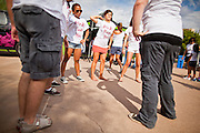 """30 JULY 2011 - PHOENIX, AZ:  Dancers warm up before dancing in a flash mob in Phoenix, AZ. About 200 people showed up at Heritage Square in downtown Phoenix Saturday morning for a flash mob coordinated by the Arizona Science Center. The mob danced to several hip-hop songs before disbanding. The event was a part of National Dance Day Activities and the First Lady's """"Let's Move!"""" physical fitness campaign.         PHOTO BY JACK KURTZ"""