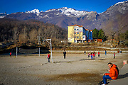 Children play games in a school playground in Bajram Curri with snow topped mountain in the Valbona Valley National Park behind on the 12th of December 2018, Albania. Bajram Curri is a town located in northern Albania, very close to the border with Kosovo, in a remote, mostly mountainous region. The town is named after Bajram Curri, a national hero who fought for ethnic Albanians, first against the Ottoman Empire and later against the Albanian government.