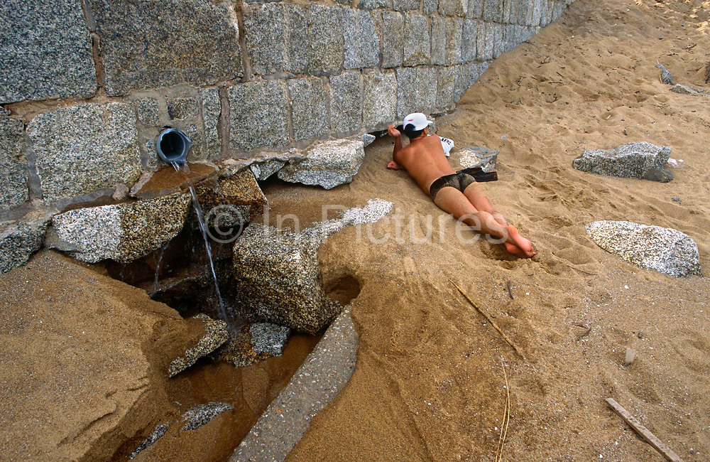 Next to a beach bather, water pours from an outlet pipe on a tourist beach on Coloane island Cheoc Van beach, Macau, China. With his face towards the course sand, the bather lies with his head towards a large wall, whose large stone blocks accommodate the pipe at the bottom. Apart from a pair of brief swimming trunks and a sun hat, he lies with ankles crossed, as if in paradise. But this seemingly industrial landscape is far from the idyllic place other tourists might wish to frequent. We do not know how filthy or indeed how pure, this water that pours out from the ground is, but the suspicion is that the pollution may affect human health. The once-Portuguese colony of Macau is now administered by China as a Special Economic Region (SER) and the official languages are Portuguese and Chinese.