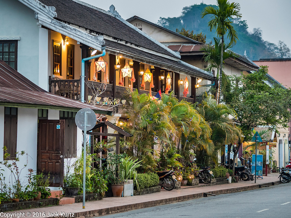 """12 MARCH 2016 - LUANG PRABANG, LAOS:  A colonial style shophouse turned into tourists' boutiques and souvenir shops in Luang Prabang. Luang Prabang was named a UNESCO World Heritage Site in 1995. The move saved the city's colonial architecture but the explosion of mass tourism has taken a toll on the city's soul. According to one recent study, a small plot of land that sold for $8,000 three years ago now goes for $120,000. Many longtime residents are selling their homes and moving to small developments around the city. The old homes are then converted to guesthouses, restaurants and spas. The city is famous for the morning """"tak bat,"""" or monks' morning alms rounds. Every morning hundreds of Buddhist monks come out before dawn and walk in a silent procession through the city accepting alms from residents. Now, most of the people presenting alms to the monks are tourists, since so many Lao people have moved outside of the city center. About 50,000 people are thought to live in the Luang Prabang area, the city received more than 530,000 tourists in 2014.      PHOTO BY JACK KURTZ"""