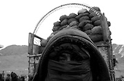<<coal distribution photo package>>..A worker shelters himself from the cold and dust before unloading bags of coal for the ICRC (International Committe for the Red Cross) inside Kabul city. (shot 2-11-02)