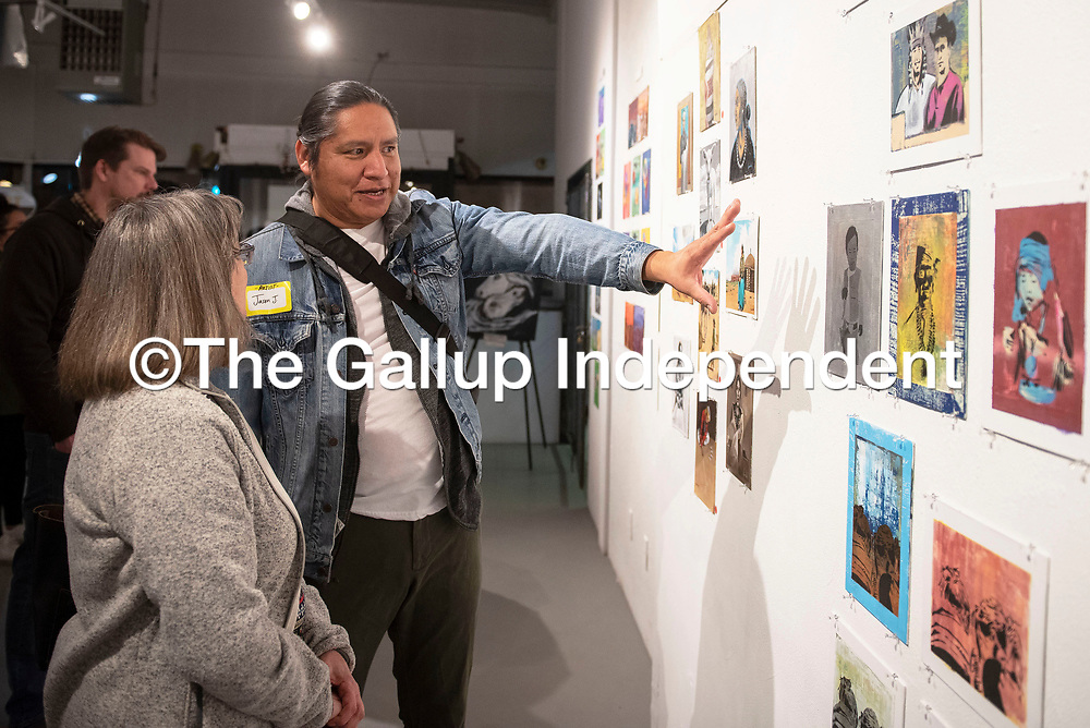 Carol Sarath, left and artist Jason John talk about his work in the 8 x 10 x 20 Artist Challenge show opening at Art123 Gallery in Gallup Saturday night. The show features 20 local artists and runs through March 7.