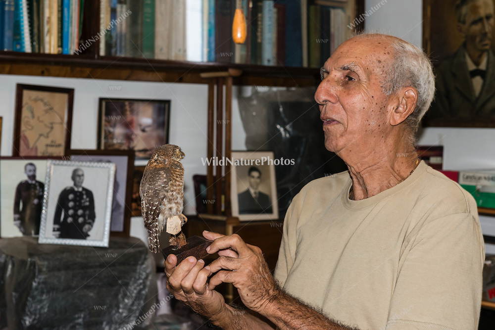 Orlando Garrido, co-author of Field Guide to the Birds of Cuba, lecturing with a mounted owl in his office in Havana, November 5, 2012