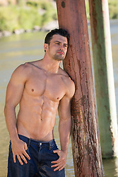 shirtless wet man in jeans leaning against a post in a river