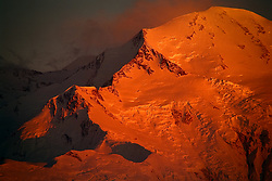 """Denali (Athabaskan for """"The High One"""") basks in the final light of sunset on a summer evening in Denali National Park and Preserve in Alaska. The snow and glacier covered mountain, part of the Alaska Range soars to a height of 20,310 feet. Denali is the tallest mountain on the North American continent. Although Mt. Everest is higher, the vertical rise of Denali is greater. This view is of the north slopes of the mountain seen from Wonder Lake."""