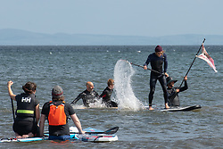 The local Surfers Against Sewage group organised a Paddle Out protest this morning on Portobello Beach. The Paddle Out is a spriritual symbol in surfing culture, usually held to commemorate the passinf of a fellow surfer and involves a group of surfers and paddle boarders forming a circle in the sea. On this occassion the paddle out in Portobello, and elsewhere across the UK, was held to highlight the plight of the ocreans and the planet to the G7 leaders meeting in Cornwall. <br /> © Jon Davey/ EEm