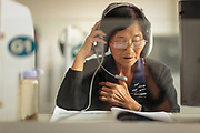 An elderly woman studies a foreign language in a language lab at a University of the Third Age (U3A). Older people can learn new languages and many other skills with state-of-the-art technology.