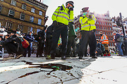 Police stand guard in front of spilt oil as members of Extinction Rebellion Youth Cambridge blocked the road outside Baringa Partners building in London on Thursday, Sept 10, 2020 - in an attempt to highlight the involvement of Schlumberger Limited in what they call 'ecocide'. Schlumberger is an oilfield services company working in more than 120 countries and has four principal executive offices located in Paris, Houston, London, and The Hague. An article at the Guardian suggests that it's ubiquitous in fossil fuel operations across the world, has more staff than Google, turns over more than Goldman Sachs, and is worth more than McDonald's – yet you won't have heard of it. XR Youth of Cambridge said that the British government gave 'Schlumberger' a no-strings-attached £150 million bailout loan as it was laying off a fifth of its global workforce. Another activist added: 'Schlumberger is hiding in plain sight here in Westminster. Every day, hundreds of people walk past this building with no idea that they're on the doorstep of a climate crime scene.'<br /> Environmental nonviolent activists group Extinction Rebellion enters its 10th and final day of continuous ten days protests to disrupt political institutions throughout peaceful actions swarming central London into a standoff, demanding that central government obeys and delivers Climate Emergency bill. (VXP Photo/ Vudi Xhymshiti)
