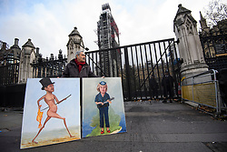 © Licensed to London News Pictures. 12/12/2018. London, UK. Artist KAYA MARR holds up artwork depicting Jacob Rees-Mogg and British Prime Minster Theresa May, outside the Houses of Parliamnet in Westminster as Prime Minister Theresa May faces a vote of no confidence from her own party. Photo credit: Ben Cawthra/LNP