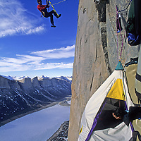 BAFFIN ISLAND, Nunavut, Canada.  Alex Lowe (MR) ascends rope above hanging camp on Great Sail Peak, on last day of month-long, Arctic big wall climb above frozen lake in Stewart Valley.