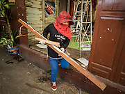 21 SEPTEMBER 2015 - BANGKOK, THAILAND: A demolition worker takes scrap out of a home being torn down near Wat Kalayanamit. Fiftyfour homes around Wat Kalayanamit, a historic Buddhist temple on the Chao Phraya River in the Thonburi section of Bangkok are being razed and the residents evicted to make way for new development at the temple. The abbot of the temple said he was evicting the residents, who have lived on the temple grounds for generations, because their homes are unsafe and because he wants to improve the temple grounds. The evictions are a part of a Bangkok trend, especially along the Chao Phraya River and BTS light rail lines. Low income people are being evicted from their long time homes to make way for urban renewal.    PHOTO BY JACK KURTZ