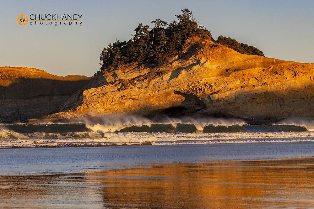 Sunrise reflection on wet sand beach at Cape Kiwanda in Pacific City, Oregon, USA