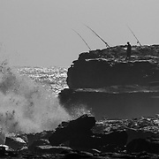 Fishermen silhouetted along the coast of Hawaii with heavy waves crashing against the lava.