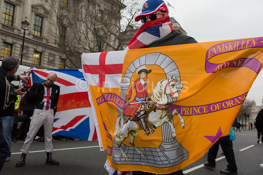 After threee and a half years of political upheavel in the British parliament, a masked man holds up a Northern Irish banner featuring the Protestant William of Orange alongside Brexiteers celebrate in Westminster on Brexit Day, the day when the UK legally leaves the European Union, on 31st January 2020, in London, England.