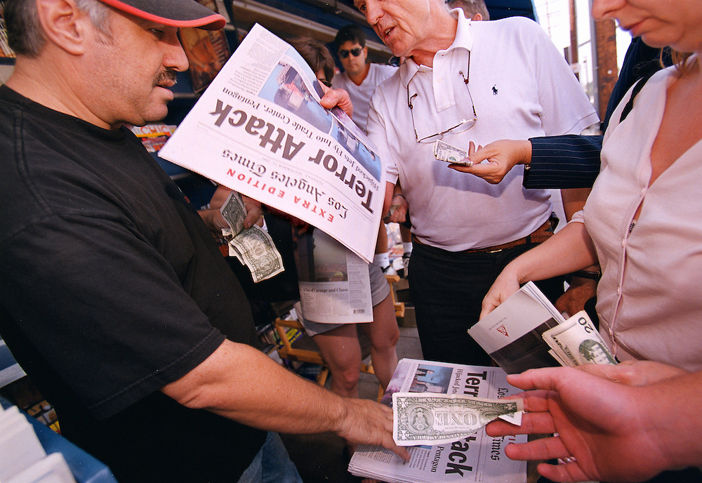 Los Angeles residents gather around a news stand on September 11, 2001 to grab an Extra Edition of the Los Angeles Times detailing the terrorist attacks that morning.
