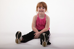 Young girl sitting on the floor with legs outstretched,