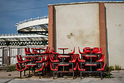Red tables and chairs removed from the old station cafe stacked up behind a wall on Folkestone Harbour Arm on the 22nd of May 2020, Folkestone, United Kingdom. Folkestone was a major passenger ferry port to Boulogne France up until September 2000.