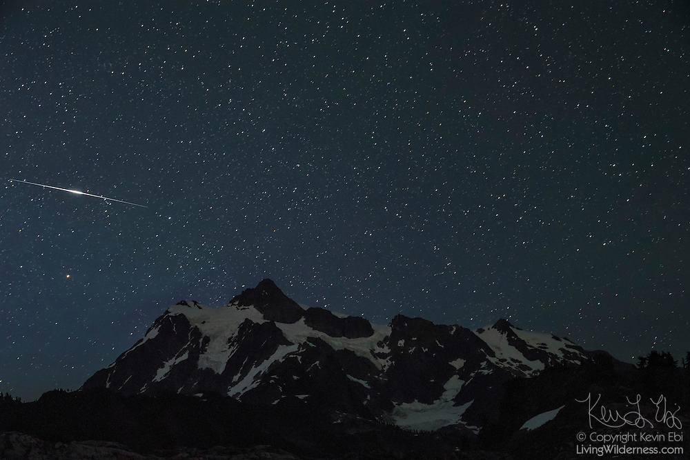 A bright fireball meteor from the Perseid meteor shower streaks across the sky over Mount Shuksan in the North Cascades of Washington state. The Perseids are an annual meteor shower that occurs in August when Earth passes through the debris of Comet 109P/Swift-Tuttle. The meteors are comet debris burning up in the Earth's atmosphere.