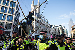 London, UK. 27th August, 2021. Environmental activists from Extinction Rebellion use three tripods to block a junction outside Mansion House underground station following a Blood Money March through the City of London on the fifth day of Impossible Rebellion protests. Extinction Rebellion were intending to highlight financial institutions funding fossil fuel projects, especially in the Global South, as well as law firms and institutions which facilitate them, whilst calling on the UK government to cease all new fossil fuel investment with immediate effect.
