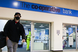 © Licensed to London News Pictures. 25/08/2020. London, UK. A man wearing a face covering walks past a branch of Co-operative Bank in Wood Green, north London. As a result of an increase in people using online banking and the impact of coronavirus on the economy, Co-operative Bank announces that it plans to cut around 350 jobs and close 18 branches. The job losses will be focused on middle management positions and head office roles. Photo credit: Dinendra Haria/LNP
