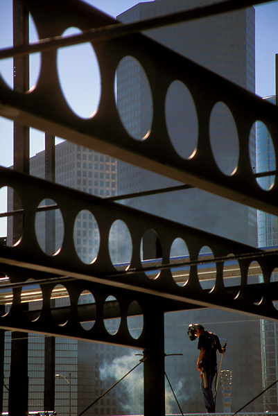 Stock photo of a worker observing construction with steel beams in foreground and office buildings in background.