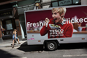 A Tesco delivery van for online purchases and woman passer-by in the City of London - the capitals financial district, on 6th June 2018, in London, England.