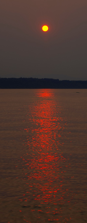 Through a thick haze of wildfire smoke, the sun casts an intense red glint on the water of Puget Sound in this view from Edmonds, Washington.