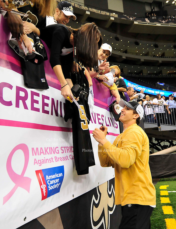 """New Orleans Saints QB Drew Brees signs autographs for fans in front of the Breast Cancer Screening Banner prior to the game against the Carolina Panthers Sunday Oct. 3,2010. The NFL has gone """"Pink"""" for October in honor of Breast Cancer Awarness. The Saints went on to win 16-14. John Carney kicked three field goals to help the Saints win.PHOTO©SuziAltman.com"""