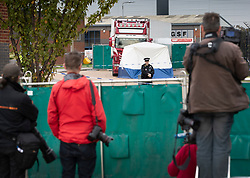 © Licensed to London News Pictures. 23/10/2019. Grays, UK. Photographers and TV crews look on as police guard a truck at Waterglade Industrial Park in Grays, Essex where the bodies of 39 people have been found. The driver, a 25-year-old-man from Northern Ireland, has been arrested on suspicion of murder. . Photo credit: Peter Macdiarmid/LNP