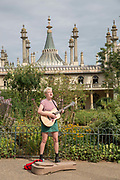 A female street busker playing the guitar in the Royal Pavilion gardens on the 19th July 2018 in Brighton in the United Kingdom. The Royal Pavilion, also known as the Brighton Pavilion, is a Grade I listed former royal residence located in Brighton, England.