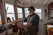 Lady Florence boat trip cruise River Ore, Orford Ness, Suffolk, England portrait boatman captain at wheel