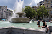 A young boy stands in chemically-treated fountains water in Trafalgar Square on Covid 'Freedom Day'. This date is what Prime Minister Boris Johnson's UK government has set as the end of strict Covid pandemic social distancing conditions with the end of mandatory face coverings in shops and public transport, on 19th July 2021, in London, England.
