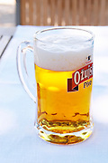 A big glass of refreshing cool beer, pivo, with white froth. Hotel and restaurant Kompas. Uvala Sumartin bay between Babin Kuk and Lapad peninsulas. Dubrovnik, new city. Dalmatian Coast, Croatia, Europe.