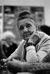 Portrait of elderly woman sitting with chin resting on hand looking thoughtful,
