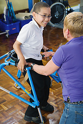 Boy with cerebral palsy using walking aid,