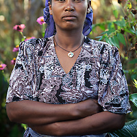 Bayush stands outside her home. ..Bayush Kassan (age 37) lives in the village of Amba Sebat, 20km from the town of Assosa with her daughter Genet (age 14) and son Destaw (age 11) in a small thatched hut without running water or electricity. Bayush is part of a cooperative of 31 women who collectively own land on which they farm vegetables. She grows sesame and other oil-seeds and her village cooperative is part of the Assosa Farmers Multipurpose Cooperative Union. The Union buy's Bayush's seed for almost double the average price paid to her by private traders. ..Growing oil seeds presents challenges for the famers of Assosa in western Ethiopia. Many of the most vulnerable are forced to sell to when they cannot be guaranteed a good price for their product. Farms are often located in isolated areas which entails huge amounts of time and effort simply getting seeds to market. Many farmers do not have the resources to properly invest in their land and are tied into exploitative loan arrangements with brokers that deny them the chance to take proper control of their farms. And, as with other agricultural products, it is those agents that process the seeds into oil that secure the greatest profit, very little of which trickles down to benefit the farmer...In response to these pressures, twenty farming cooperatives have formed the Assosa Farmers Multipurpose Cooperative Union. By working together, individual farmers are able to pool their resources and squeeze out exploitative agents and brokers. The Union has sufficient capital that it can afford to wait for prices to reach a level at which it is profitable to sell seeds to market. The Union provides loans to constituent members together with training and advice to help farmers make better use of their land. And by collectively hiring vehicles through the Union, farmers need not spend so much time ferrying their produce to market. ..All these measures benefit farmers and have now provided the Assosa Farmers Multipurpose C