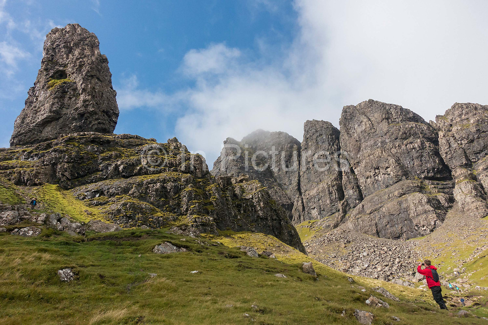 A man takes a photograph at The Old Man of Storr on the 3rd September 2016 on the Isle Of Skye in Scotland in the United Kingdom. The 'Old Man' is a large pinnacle of rock that stands high and can be seen for miles around. Forming part of the Trotternish ridge, the Storr was created by a massive ancient landslide, and has become a popular walking and tourist destination.