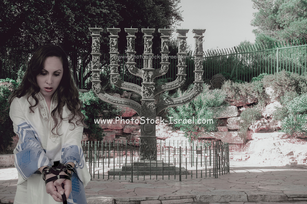 Digitally enhanced image of Religious Compulsion concept. Woman wrapped in leather straps resembling Phylacteries straps and Jewish prayer shawl (tallith) The Menorah sculpture by Benno Elkan at the entrance to the knesset, the Israeli parliament, in the background