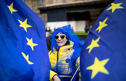 "© Licensed to London News Pictures. 13/03/2019. London, UK. An anti-Brexit protester wearing a blue wig and yellow sunglasses at a protest outside Parliament as MPs continue to debate a series of key votes this week. MPs will vote on whether to remove the option of a ""no deal"" departure from the EU today, after Prine Minister Theresa May's proposed deal was defeated for a second time last night. Photo credit: Rob Pinney/LNP"