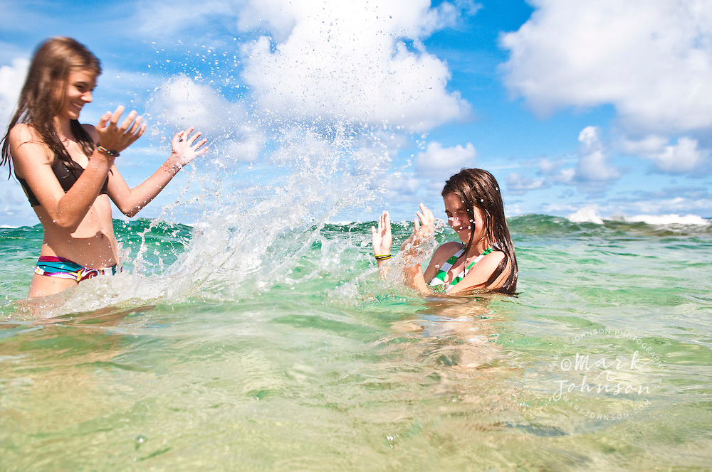 2 Teenage girls splashing water on each other at beach, Kauai, Hawaii, USA people ****Model Release available