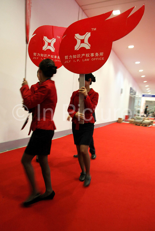Representatives from a intellectual property law office carry promotional placards at a technology fair in Shenzhen, China on 17 November 2009.