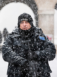 © Licensed to London News Pictures. 27/02/2018. London, UK. A policeman stands guard on Horse Guards Parade in central London as heavy snow falls. Severe cold, blizzards and heavy snow are expected for the rest of the week as the 'Beast from the East' brings freezing Siberian air to the UK. Photo credit: Rob Pinney/LNP
