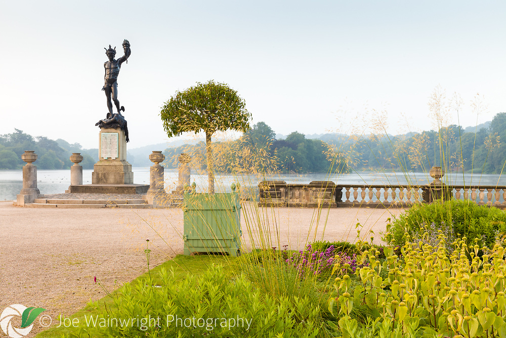 The statue of Perseus and Medusa at Trentham Gardens, Staffordshire - with the lake at Capability Brown landscape in the background. The foreground is the Italian Garden, designed by Tom Stuart-Smith, planted Portuguese laurels, Stipa gigantea and Phlomis russeliana. This image is available for sale for editorial purposes, please contact me for more information.