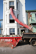 Builders waste shute clearing rubbish from a building development into a truck, Aldeburgh, Suffolk, England