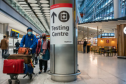 © Licensed to London News Pictures. 08/01/2021. London, UK. Passengers walk past a Covid-19 Testing Centre sign at London Heathrow as Mayor of London, Sadiq Khan declares a Major Incident as cases continue to spread throughout the capital. This week, Prime Minister Boris Johnson plunged England into a 3rd lockdown as he ordered schools to close and workers to work from home as the government brings in the army to ramp up vaccinations across the country. Photo credit: Alex Lentati/LNP