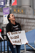 """San Francisco, USA. 19th January, 2019. The Women's March San Francisco begins with a rally at Civic Center Plaza in front of City Hall. A young woman stands on the stage with others representing the Young Women's Freedom Center. She shouts with the crowd and holds a sign reading: """"I stand for chicana women!"""" Credit: Shelly Rivoli/Alamy Live News"""